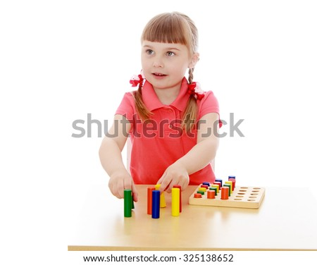 Adorable little blonde girl with short bangs and tiny braids that are braided in red ribbons in a Montessori kindergarten. Girl playing at the table with Montessori material-Isolated on white - stock photo