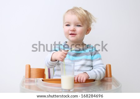 Adorable little blonde toddler girl in blue stripes sweater drinking milk from the glass with straw sitting indoors in high feeding chair against white wall