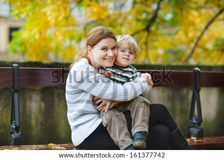 Adorable little boy and mother sitting on a bench in autumn city - stock photo