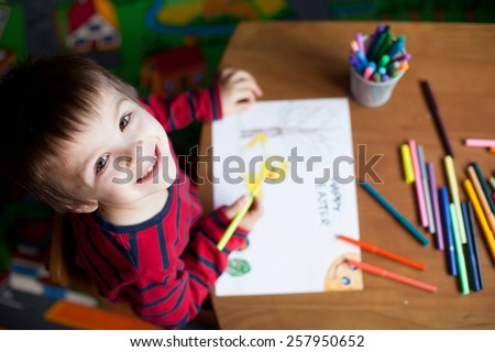 Adorable little boy, drawing picture for easter at home, having fun, smiling at camera, shot from above - stock photo