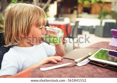 Adorable little boy drinking fresh apple juice in a restaurant - stock photo