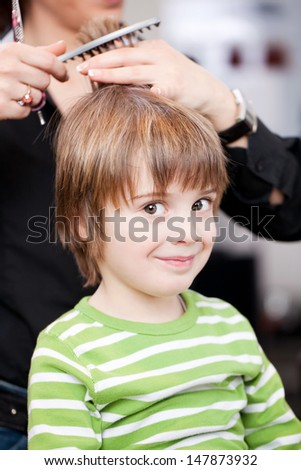 Adorable little boy getting a hair cut by a professional stylist at a hairdressing salon giving the camera a sideways look and smiling - stock photo