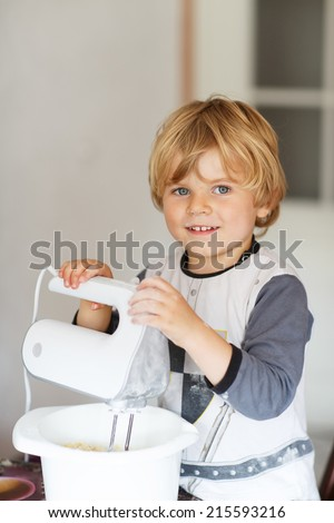 Adorable little boy helping and baking pie in home''s kitchen, indoor. Mixing dough. - stock photo