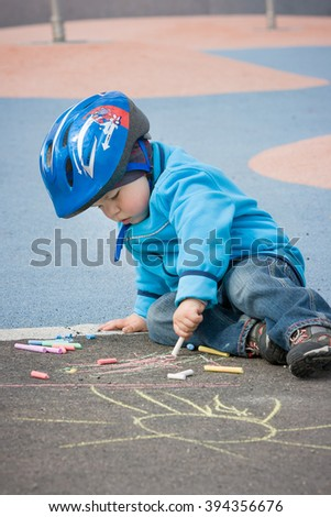 Adorable little boy in blue jacket and his bicycle helmet sitting on the road and drawing with chalk. Happy childhood. Leisure activities with children outdoors. Preschool kid painting on the asphalt. - stock photo