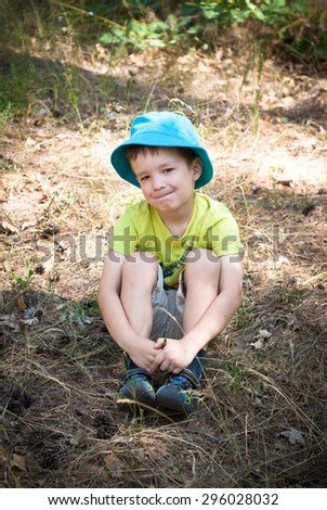 Adorable little boy in the grass in summer - stock photo