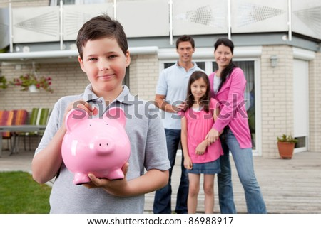 Adorable little boy inserting coin in a piggy bank with her family in background - stock photo