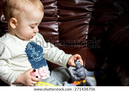 Adorable little boy is playing with toy animals sitting on a armchair - stock photo