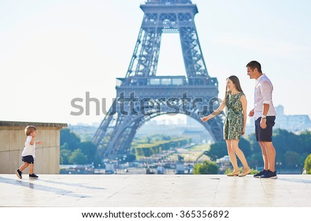 Adorable little boy making his first steps in Paris near the Eiffel towe and running to his parents - stock photo