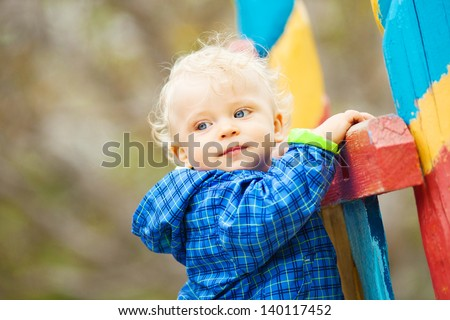 Adorable little boy playing on playground at park.   - stock photo