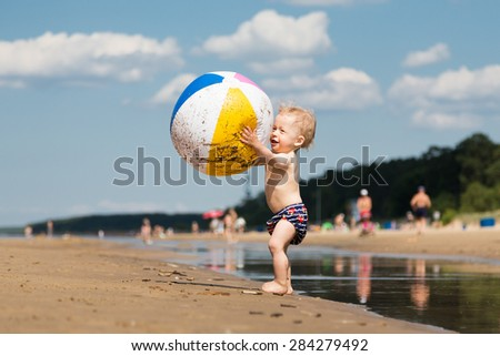Adorable little boy playing with big beach ball near the water. - stock photo