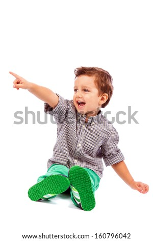 Adorable little boy pointing at something isolated on white background - stock photo