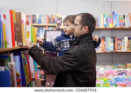 Adorable little boy, sitting in a book store, looking at books - stock photo
