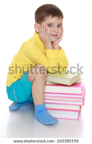Adorable little boy sitting next to a pile of books - isolated on white. - stock photo