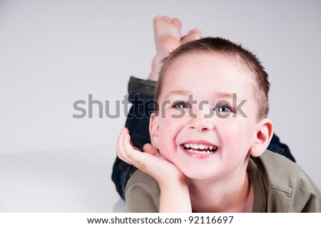 adorable little boy smiling in a studio - stock photo