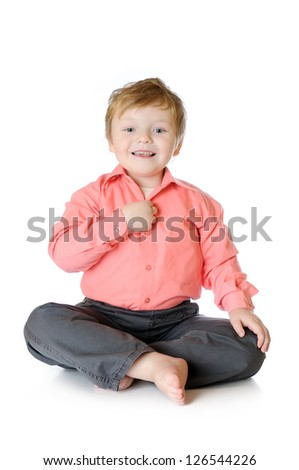 Adorable little boy smiling, sitting on the floor, studio shot, isolated on white background