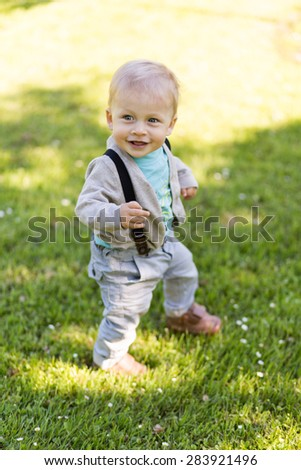 Adorable little boy standing in the grass and smiling, in summer day.  - stock photo