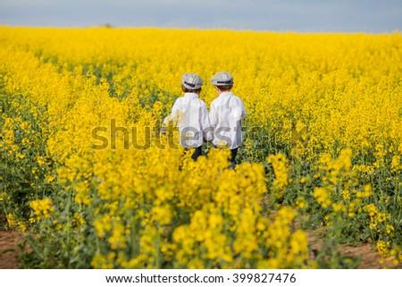 Adorable little boy, standing in yellow oilseed rape field, backwards, feeling happy and free - stock photo