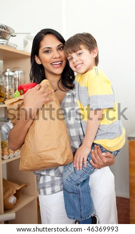 Adorable Little boy unpacking grocery bag with his mother in the kitchen - stock photo
