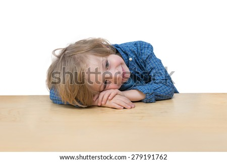 Adorable little boy with blonde hair, blue eyes, smiling on the wooden table edge isolated over white background 