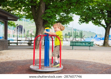 Adorable little by having fun on playground - stock photo