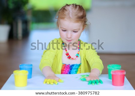 Adorable little child, blonde artistic toddler girl painting and drawing with colorful finger paints indoors at bright room at home or kindergarten. - stock photo