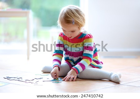 Adorable little child, blonde toddler girl, playing with puzzles sitting on the tiles floor next to a big window at home or kindergarten - stock photo