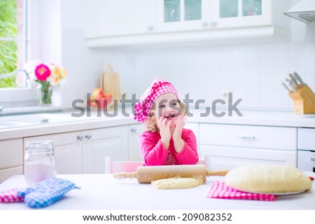 Adorable little child, funny curly toddler girl in a pink chef hat baking a pie rolling dough sitting in a white sunny kitchen with big window - stock photo