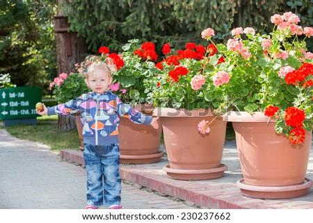 Adorable little child girl in park near flower Bed in summer day. Use it for baby, parenting or love concept - stock photo