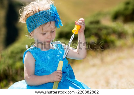 Adorable little child girl with bubble blower on grass on meadow. Summer green nature .  Use it for baby, parenting or love concept - stock photo