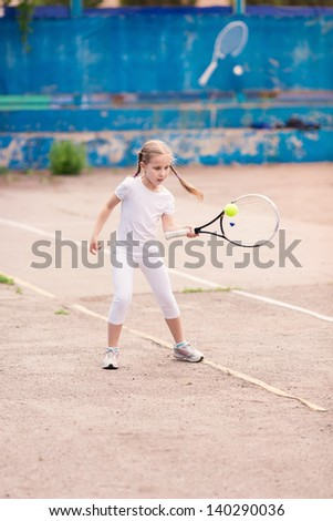 Adorable little child playing tennis with racket and a ball on tennis court - stock photo