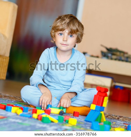 Adorable little child playing with lots of colorful wooden blocks indoor. Active kid boy  having fun with building and creating. People, lifestyle, childhood, nursery concept - stock photo