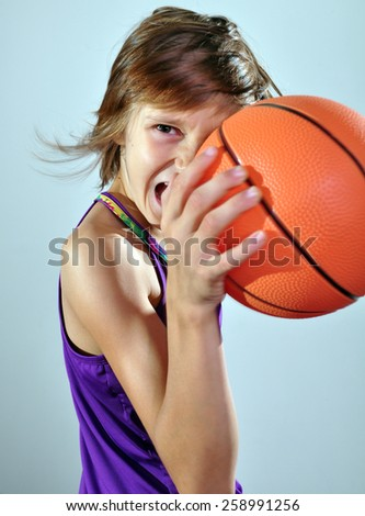 adorable little elementary girl exercising with a ball - stock photo