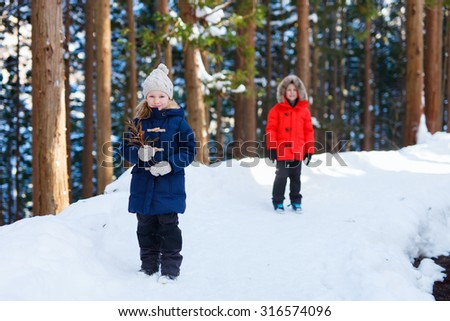 Adorable little girl and cute boy outdoors in forest or park on beautiful winter day - stock photo