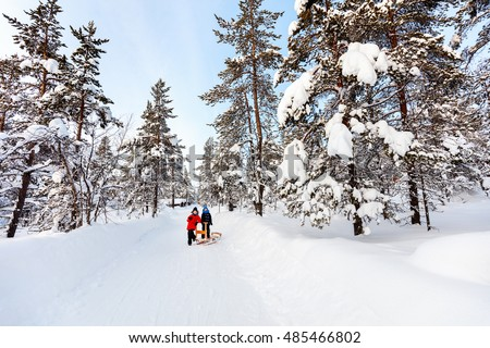 Adorable little girl and cute boy outdoors on beautiful winter day having fun playing in snow