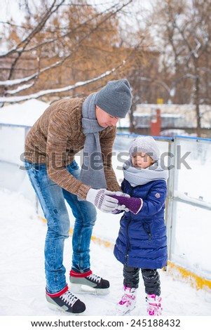 Adorable little girl and happy dad on skating rink outdoor