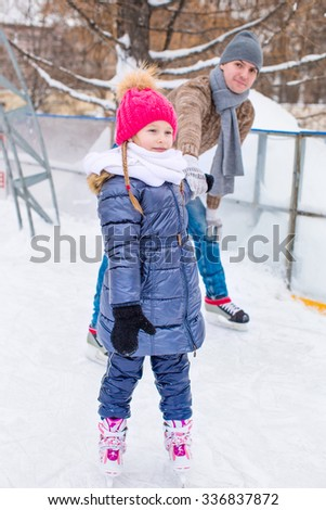 Adorable little girl and happy father on skating rink outdoors - stock photo