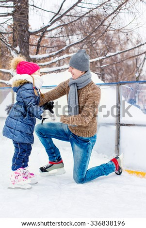 Adorable little girl and happy father on skating rink outdoors at beautiful summer day - stock photo