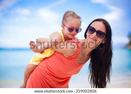 Adorable little girl and happy mom during tropical beach vacation - stock photo