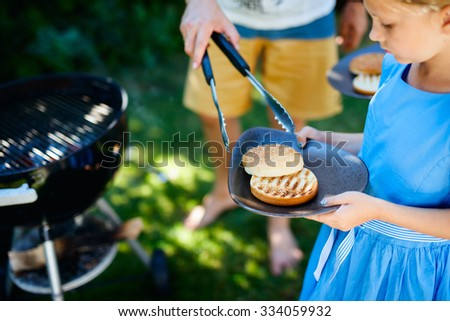 Adorable little girl and her family cooking delicious homemade burger outdoors on summer day - stock photo