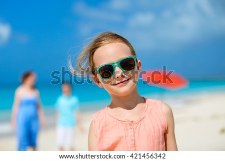 Adorable little girl and her family on a tropical beach vacation - stock photo