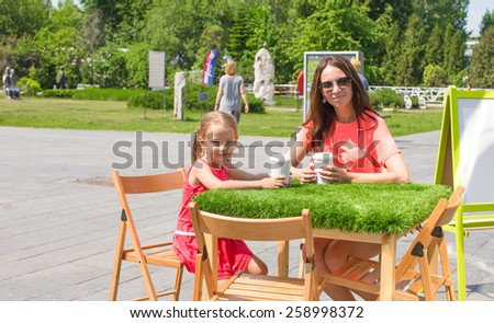 Adorable little girl and mom at outdoor cafe on warm day - stock photo