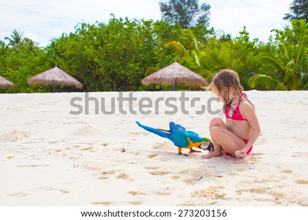 Adorable little girl at beach with colorful parrot - stock photo