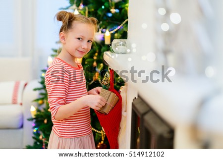 Adorable little girl at home beautifully decorated for Christmas with fireplace, tree, stockings and lights