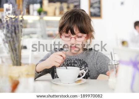 Adorable little girl at restaurant having breakfast - stock photo