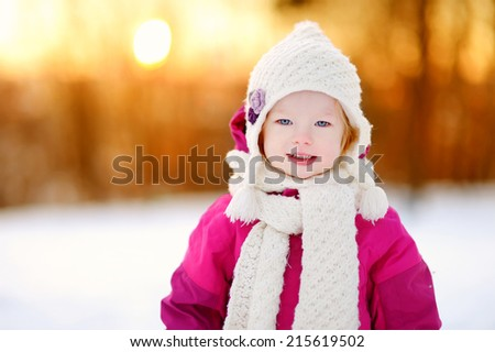Adorable little girl at sunset on a beautiful winter day