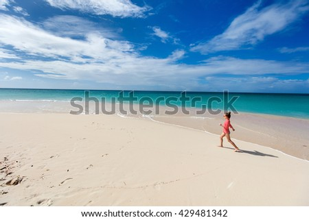Adorable little girl at unique pink sand beach on Barbuda tropical island in Caribbean