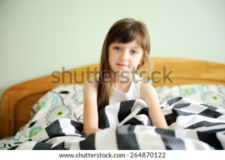 Adorable little girl awaked up in her bed on sunny morning