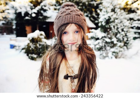 Adorable little girl, beauty school aged in a pastel colors  knitted sweater, gold skirt, fur vest and brown hat, playing in snow, having fun outdoors in a beautiful sunny  winter park - stock photo