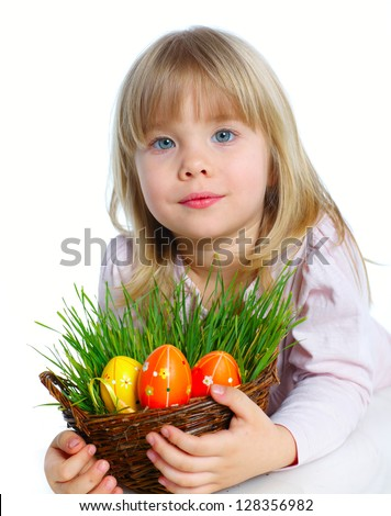 Adorable little girl collecting Easter eggs and grass in her basket - stock photo