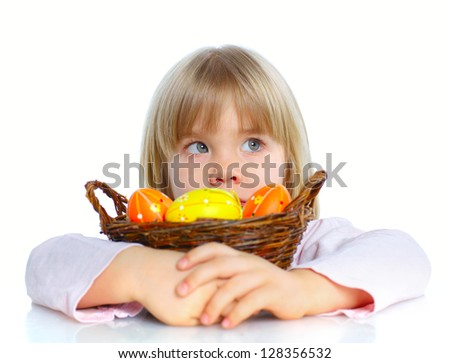 Adorable little girl collecting Easter eggs in her basket - stock photo